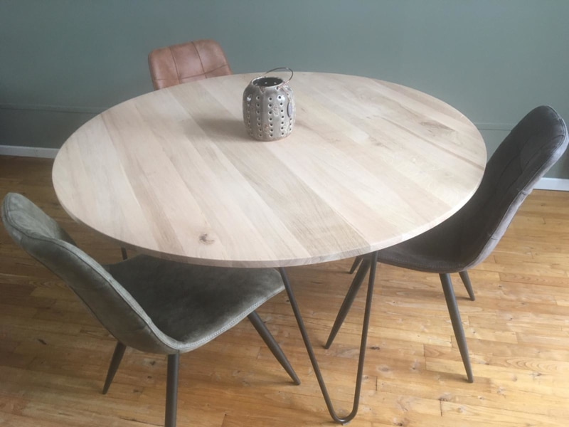 round oak table with a rejuvenated edge with black base