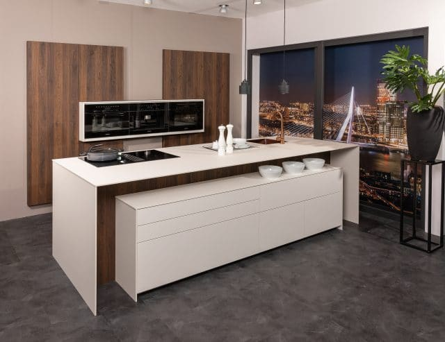 Een keuken die volledig greeploos is, met warme houtpanelen en een wit werkblad, die zorgen voor een huiselijk en strak karakter.